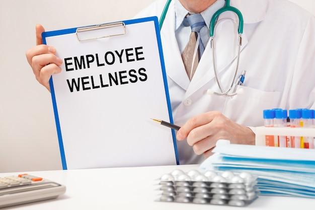 Dokter houdt papier met inscriptie employee wellness, stethoscoop en pillen op tafel