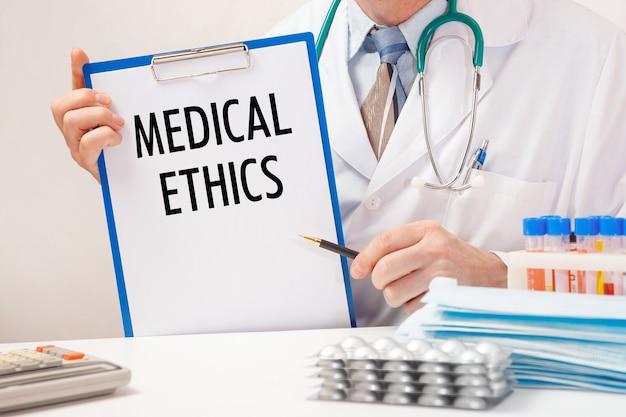Dokter houdt papier met inscriptie medische ethiek, stethoscoop en pillen op tafel