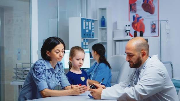 Dokter houdt pillenfles vast en schrijft instructies terwijl hij met de ouder in de kliniek praat. arts, specialist in geneeskunde die medische diensten verleent consultatie diagnostische behandeling in het ziekenhuis
