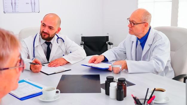 Dokter houdt presentatie over symptomen van patiënten voor medisch team dat onderzoeksstappen plant. medisch team met conferentie over mensenziekte zittend in ziekenhuiskantoor