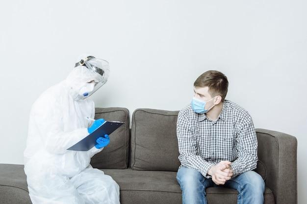 Dokter in beschermend pak van pbm legt de getuigenis van de patiënt vast