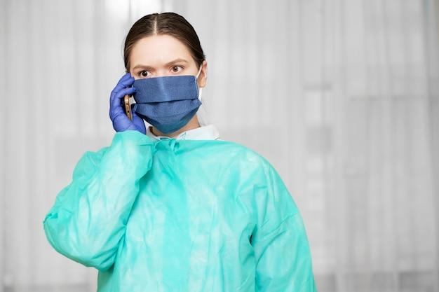 Dokter in beschermende uniform houdt telefoon in de hand, vrouw belt een ambulance op de telefoon, sociale netwerken