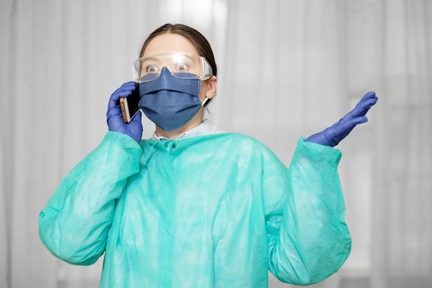 Dokter in beschermende uniform houdt telefoon in de hand, vrouw roept een ambulance op de telefoon, emotionele arts