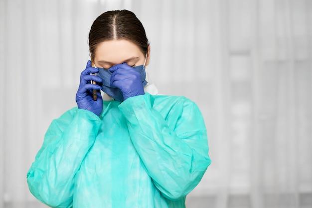 Dokter in beschermende uniform houdt telefoon in de hand, vrouw roept een ambulance op de telefoon, sociale netwerken, vermoeide dokter