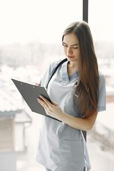 Dokter in blauw uniform. meisje met een stethoscoop om haar nek. vrouw met lang haar.