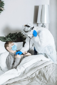 Dokter in een beschermend pak, masker en handschoenen luistert thuis voor nieuwjaar en kerstmis met een stethoscoop naar de ademhaling van de patiënt