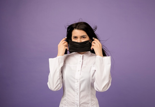 Dokter in een medische jurk draagt een zwart medisch masker op paars