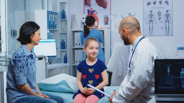 Dokter in gesprek met klein meisje zittend op bed in medisch kantoor gezondheidszorgbeoefenaar, arts, specialist in geneeskunde die gezondheidszorgdiensten verleent, diagnostische behandeling in het ziekenhuis
