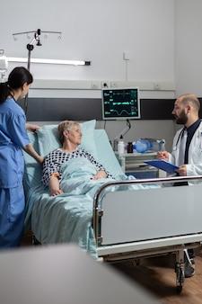 Dokter in gesprek met oudere patiënt die naast bed in ziekenhuiskamer zit en expertise geeft voor behan...