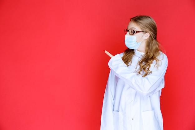 Dokter in gezichtsmasker die naar links wijst.