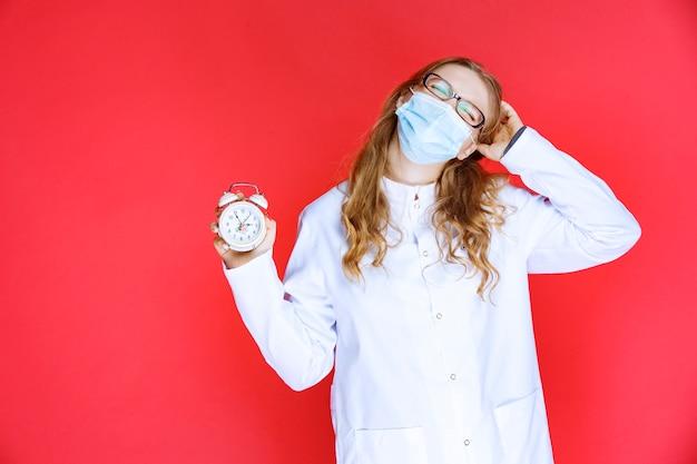 Dokter in gezichtsmasker met een klok en ziet er verward uit.