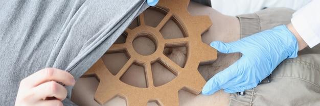 Dokter in handschoenen die de buik van de patiënt onderzoekt met diagnostiek van de houten uitrusting en