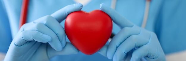 Dokter in handschoenen houdt een rode hartclose-up vast