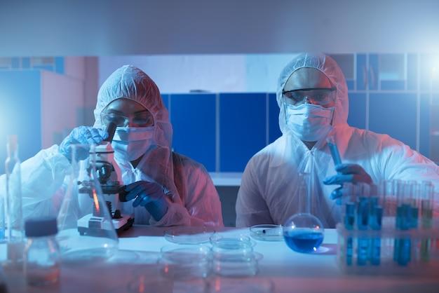 Dokter in het laboratorium analyseert monsters onder een microscoop. farmaceutisch behandelingsconcept.