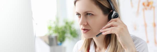 Dokter in koptelefoon met microfoon aan tafel zitten en kijken naar computerscherm