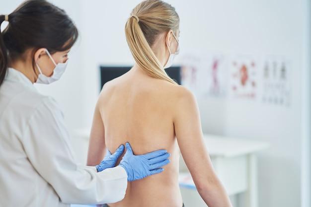 Dokter in masker die borst controleert bij haar patiënt
