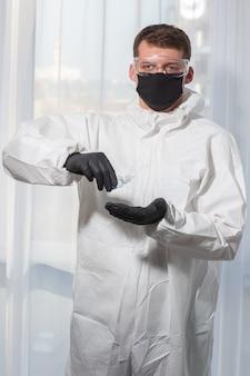 Dokter in pbm-uniform en handschoenen behandelt handen met antisepticum. corona-uitbraak. concept van covid-19 quarantaine. arts en medische zorg. persoonlijke beschermingsmiddelen stop virus.