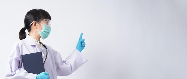Dokter in uniform wijst naar een leeg gebied. het dragen van blauwe medische latexhandschoenen en een doorzichtige veiligheidsbril en een groen n95-masker om epidemisch virus te voorkomen. aziatische arts. handgebaar. medische stethoscoop. virus boek