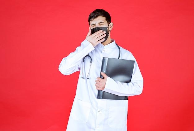 Dokter in zwart masker met een zwarte map en ziet er moe en slaperig uit.