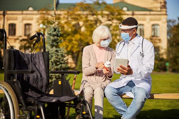 Dokter informeert een oudere vrouw over drugsgebruik terwijl ze een tablet gebruikt en buiten zit op een zonnige dag