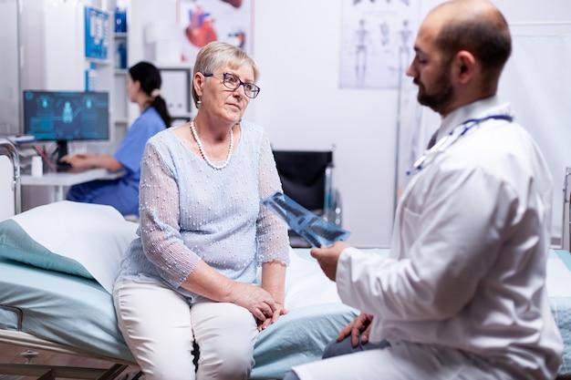 Dokter kijkt naar longröntgenfoto van senior vrouwelijke patiënt tijdens medisch onderzoek in ziekenhuiskamer