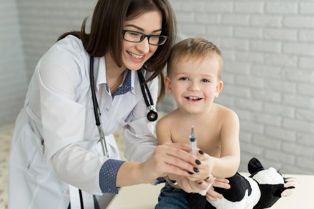 Dokter kinderarts speelt voor de injectie met de jongen.