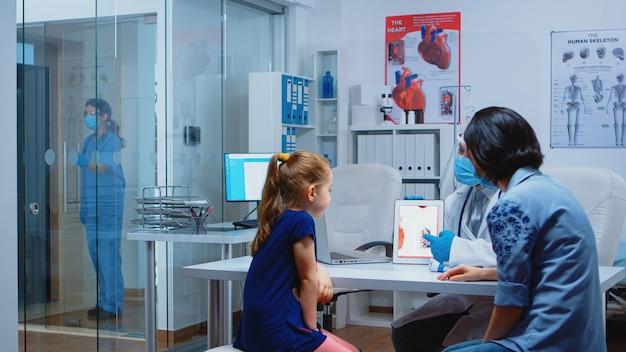 Dokter legt aan het kind de functies van het hart uit met behulp van een tablet en het dragen van gezichtsbescherming. kinderartsspecialist met handschoenen die consultaties in de gezondheidszorg verlenen tijdens covid-19