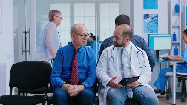 Dokter legt behandeling uit aan senior man in de wachtruimte van het ziekenhuis. vrouw met looprek die bij medisch onderzoek aankomt.