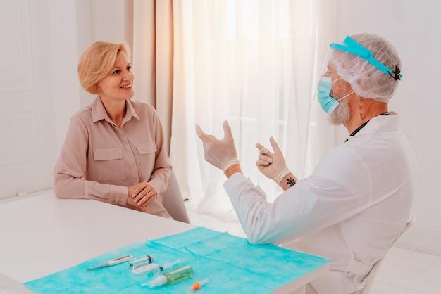 Dokter legt de patiënt informatie uit over het covid-virus