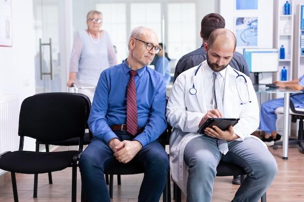 Dokter legt testresultaten uit aan senior man in wachtruimte van ziekenhuis