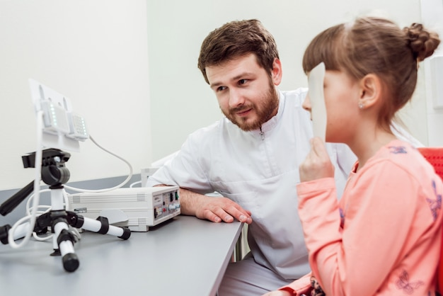 Dokter legt uit hoe oogheelkundige apparatuur te gebruiken.