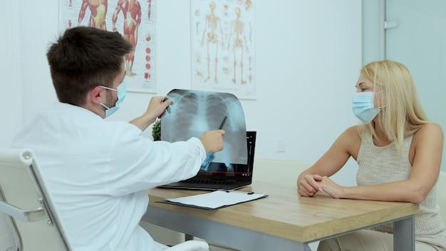 Dokter legt x-ray borstresultaat in computerlaptop uit aan zieke vrouwelijke patiënt in onderzoekskamer in het ziekenhuis. mannelijke medic draagt gezichtsmasker tijdens covid pandemie om infectie te voorkomen.
