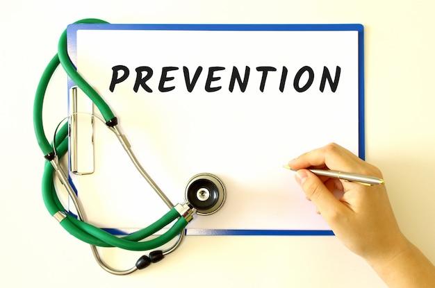 Dokter maakt de inscriptie prevention in het document folder en stethoscoop
