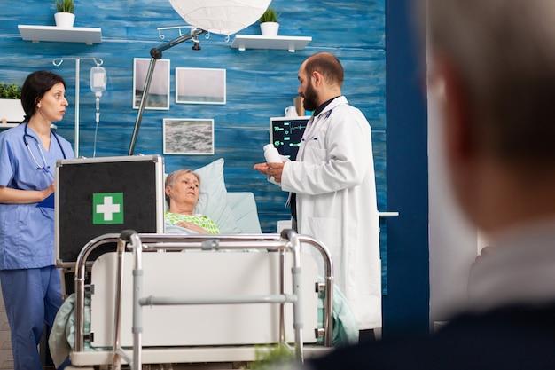 Dokter man bespreekt medicamenteuze behandeling met gepensioneerde senior zieke vrouw die medische pillen voorschrijft tegen ziekte. sociale diensten verpleging bejaarde gepensioneerde vrouw. hulp in de gezondheidszorg