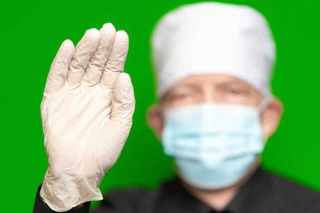 Dokter man met chirurgisch gezichtsmasker op defocus voorgrond zet palm van zijn hand naar voren in beschermende latex handschoen voorgrond, golven bij zijn hand, hallo of stopbord. concept van bescherming, veiligheid op groen