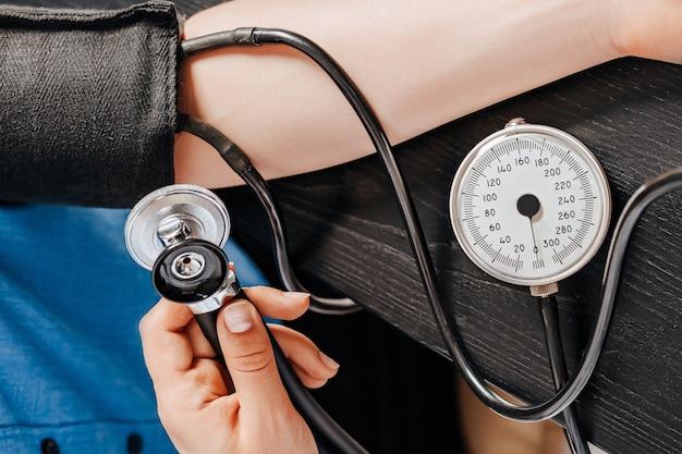 Dokter meet de bloeddruk met een tonometer aan een vrouwelijke patiënt bij een medische afspraak in een kliniek