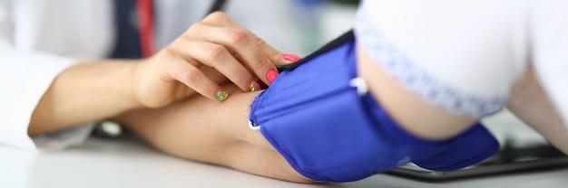 Dokter meet de druk op de patiënt in het medische kantoor