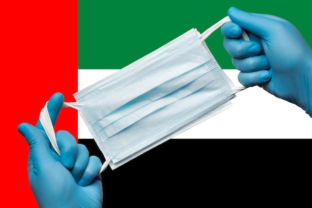 Dokter met ademhalingsmasker in handen in blauwe handschoenen op achtergrond nationale vlag van verenigde ar...