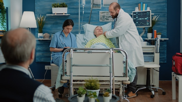 Dokter met behulp van stethoscoop op zieke senior vrouw in ziekenhuisbed