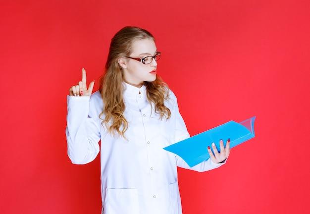 Dokter met een blauwe map die ergens of iemand wijst.