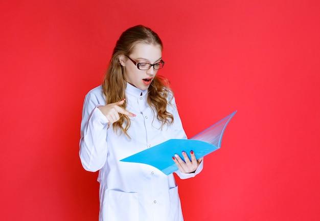 Dokter met een blauwe map kijkt verrast.