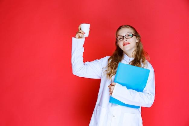 Dokter met een blauwe map met een kopje water.