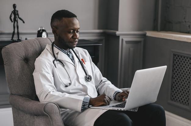 Dokter met een donkere huid praten over skype zoom met een laptop. hoge kwaliteit foto