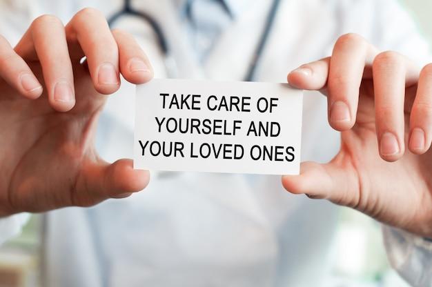 Dokter met een kaart met tekst zorg voor jezelf en je geliefdeen in beide handen