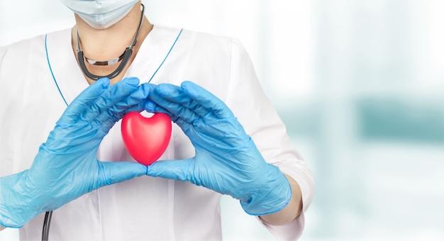 Dokter met een rood hart op ziekenhuiskantoor. geneeskunde en gezondheidszorg concept, gezondheidszorg liefde, geven, hoop en familie concept.