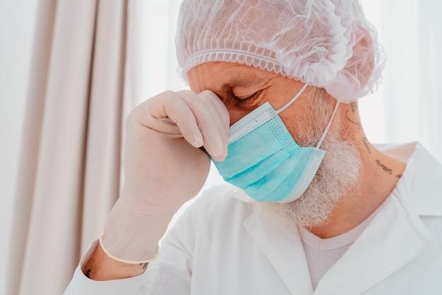 Dokter met gezichtsmasker en gezichtsbeschermer is moe van de covid-viruspandemie