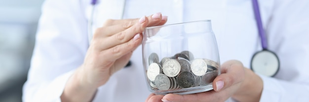 Dokter met glazen pot met munten close-up betaald geneeskunde concept