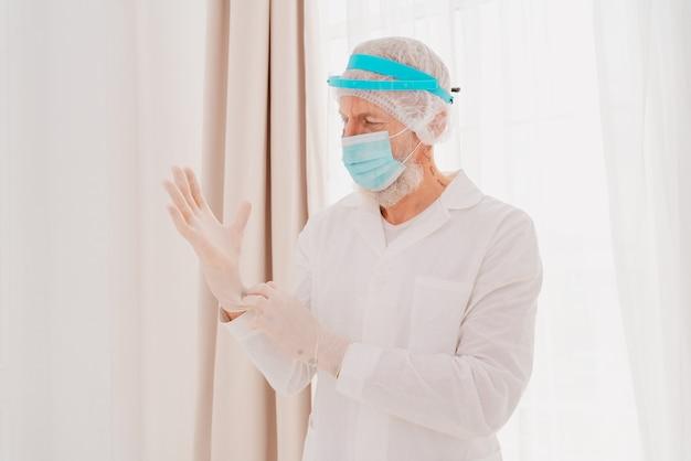 Dokter met masker en gezichtsbeschermer is klaar om in het ziekenhuis te werken