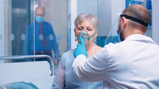 Dokter met masker en vizier helpt oude dame te ademen met een ademhalingszuurstofmasker terwijl ze op een ziekenhuisbed zit in een moderne privékliniek. coronavirus covid-19 uitbraak gezondheidszorg crisis.