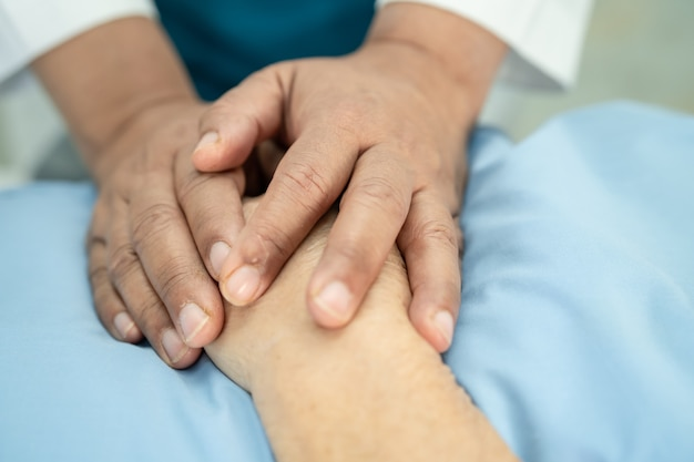 Dokter met ontroerende handen aziatische senior of oudere oude dame vrouw patiënt met liefde, zorg, helpen, aanmoedigen en empathie op verpleegafdeling ziekenhuis, gezond sterk medisch concept